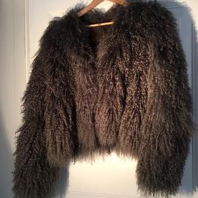 Kort langhåret rulamsjakke fra Sabine Poupinel. Længde ca 50, bredde over bryst ca 52, ærmelængde ca 68. Nypris 4500 sælges for 2000 plus porto. Bemærk ny pris.