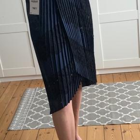 Flot mørkeblå plisseret nederdel fra Zara med sorte blonder. God elastik om livet passer både en str xs, s og lille m. Aldrig brugt og med prismærke.