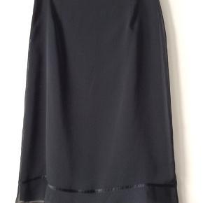 Fin og let sort nederdel i 100% polyester.str.44 Taljemål 80 cm Længde 69 cm