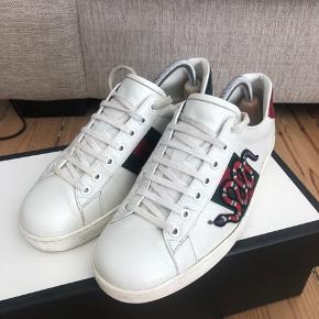 Jeg sælger hermed mine Gucci sneakers i str 42  Ny pris: 550 euro (købt i Paris) Alt medfølger  De er i super fin stand, dog er den grønne hæl lidt beskadiget
