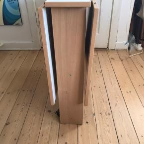 Slå-ud spisebord - hvidt med træ kanter. Vingerne kan tages af. Bordet har få mærker.   Længde foldet-ud: 117 cm Længde foldet: 23 cm Bredde: 79 cm Højde: 72 cm