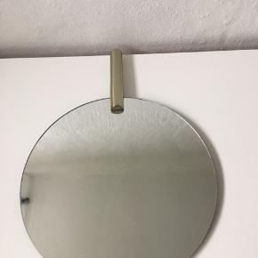 Rundt spejl med messingstang som pynt, 35 cm i diameter.