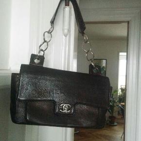 Tasken er produceret i begrænset antal og er unik på grund af de trykte Chanel logoer på og i tasken. Taske låsen og kæden er lavet af titanium så de aldrig bliver slidt eller ridset. Tasken er meget velholdt og næsten som ny. Tasken måler  30 cm x 16 cm.