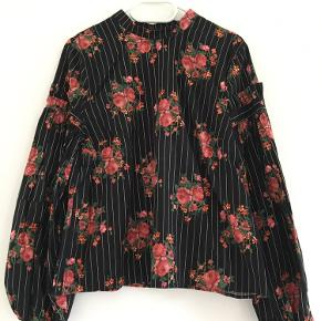 Sort skjorte med striber og blomsterprint i str. 44. Er meget lille i størrelsen, så den svarer nok nærmere til str. 38-40. Har aldrig været brugt