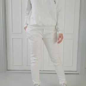 Hvidt alt bestående af bluse og bukser. Flot materiale med 3D blomster mønster. Bukserne har aldrig været brugt og har stadig prismærke på. Blusen har været brugt et par gange. Bukser str. M Bluse str. S