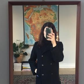 Klassisk sort uldfrakke fra det franske luksusmærke, Le Gazik. Skræddersyet model. Mangler knap og har lidt slid i ulden som billederne viser.