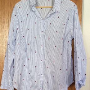 """Der står ikke noget mærke på skjorten, men den er lavet i Italien. De røde """"pletter"""" er små mariehøns, og ellers er den blå- og hvidstribet (smalle blå striber) Prisen er ekskl. porto."""