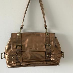 Superflot guldfarvet taske købt i USA for 10 år siden, men har ligget i min skuffe siden da. Aldrig brugt. Mærket er Kenneth Cole.