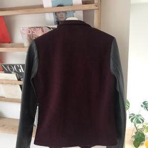 Super flot uldjakke med læderærmer fra HAN Kjøbenhavn. Jakken er ubrugt og fremstår i perfekt stand