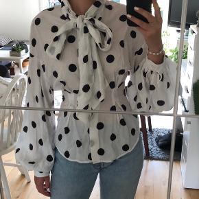 Super fin polkaprikket skjorte, med bindebånd og pufærmer. Den går ind i taljen og giver et flot timeglasfigurs look. Den er dsv kun brugt et par gange. Overhovedet ikke noget man kan se. Kan hentes i Karise eller sendes hvis køber betaler fragt.🥰