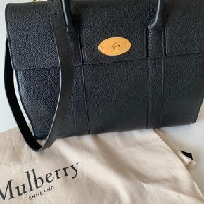 Flot sort Mulberry Bayswater with strap - købt i Mulberry New York i november 2019. Ikke brugt i hele perioden og fremstår derfor i meget pæn stand. Dustbag medfølger. E-Kvittering haves på mail og tasken er registreret ved Mulberry med forlænget garanti til 18 mdr.  Højde 29,5 Bredde 32-44 Dybde 17