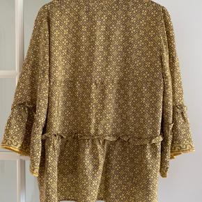 Super smuk bluse i de smukkeste gyldne farver Der er en lille guldknap foran og ved snørerne, hvilket passer flot i til farven. Størrelsen er S/M Længde foran 60 cm, bagved 70 cm  Bredde over bryst ca 52 x 2 cm NB! Lille hvid plet bag på skjorte