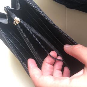 Rigtig fin Prada pung, købt brugt så har ikke kvit. Den har en fejl indeni ved lynlåsen men ikke noget man lægger mærke til når man bruger den. Der er plads til meget og ingen store tegn på slid udover den lille fejl indeni.   Skriv for mere info, vi kan snakke om prisen ;)