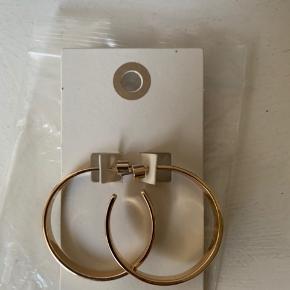 'Guld' belagte 'metal' creoler / Hoops fra UO.  Nye / ubrugte. sælges for under 1/2 pris plus porto! Diameter 35 mm og bredde knap 4 mm Sælges for 50 plus porto (nypris 135) Porto 20,- hvis brevpost via postnord.