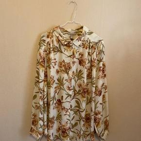 Flot hvid skjorte med blomstret print fra H&M. Kan kæbes i butikkerne nu og er ikke brugt.