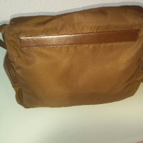 Tasken måler: 25 cm x 22 cm.