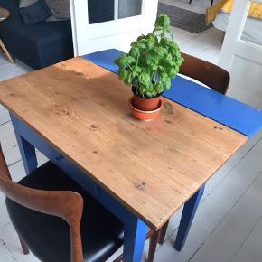 Fint lille bord med blåmalede ben + lille plade som kan vippes op og ned efter behov! Jeg har både haft glæde af at bruge bordet som skrivebord og spisebord. Der er også en lille skuffe i. Bordet er 75cm højt, 82 cm i bredden og 44 cm i dybden uden plade, 66cm med pladen slået op. Kan afhentes i indre by!