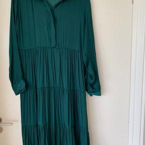 Flot dyb mørkegrøn kjole.  Lang, går til under knæene. Lækkert blødt, blankt stof. 100% polyester.  Brugt få gange. Ingen huller, revner eller lign.