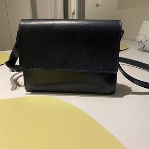 Flot blå taske fra ganni. Den har indvendige tegn på slid. Knappen på klappen er faldet af, men følger med og kan påsættes igen.