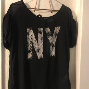 Varetype: T-shirt Farve: Sort Oprindelig købspris: 199 kr.  Fed t- shirt fra Vila.  Aldrig brugt da den desværre er for stor til mig.