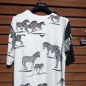 Flot bluse, næsten ikke brugt. Der er zebraer på ryggen og forstykket og den ene ærme, ven halsudskæringen er der 2 små snore med en perle i hver, og en lille slids i siden, en utrolig fin bluse. Brystmål 2 x 62 cm Længde 80 cm