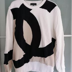 Rigtig fed Chanel bluse i hvid/beige, med klassisk Chanel logo. It str 42. Rigtig god stand. Bøgle medfølger.