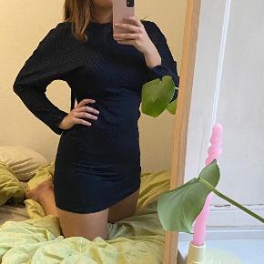 Fin tætsiddende kjole i skinnende materiale med sorte detaljer. Perfekt som cocktailkjole. Lynes på ryggen og har en høj hals med et fint langt bindebånd som bindes ved nakken (kan ses løsthængende på første billede). Skriv for mere info 💙🤩