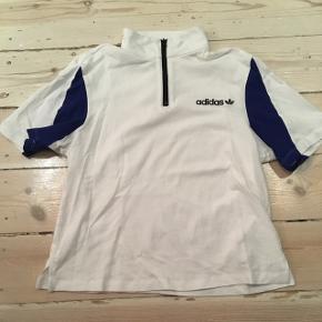 Lidt tætsiddende crop t shirt med lynlås fra adidas, hvid med mørkeblå striber