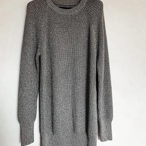 Flot strik i sølvmetallic. Blød og behagelig kvalitet. Kan bruges som kort kjole. Passer en 34/36. Brugt 1 gang og er som ny. Bytter ikke.