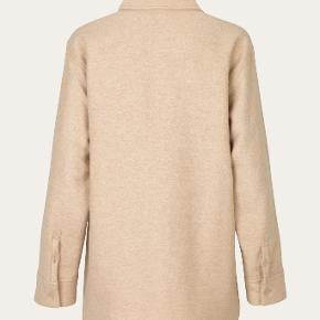 Super fin Silvi Shirt fra Stine Goya. Uldskjorte / efterårs jakke. - -Knappes foran To patchlommer i en skinnende lys sandfarve Løst / Oversized fit  Fremstillet af genbrugsuld og bæredygtig EcoVero-blanding.  Nypris 2400 ,-