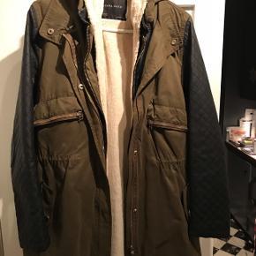 Sælger army grøn vinterjakke med hætte og sorte ærmer. Der er for i som kan knappes af. Den kan lynes op i siderne og der er snor i taljen.