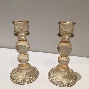 Søde lysestager i glas med en gylden farve. 15 cm høje.