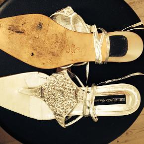 Varetype: Fede flade sultanagtige sandaler med bindebånd Farve: Hvid m. sølv Oprindelig købspris: 799 kr.  Fede flade sultanagtige sandaler med bindebånd i hvide med sølv pailletter.