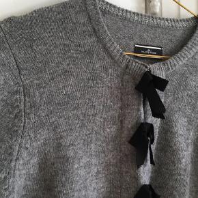 Lækker grå kort cardigan. Style: Mazika. 100% uld. Fremstår som ny. Lukkes med hægter. Længde 50cm. Det er str. L, men svarer mere til str. M