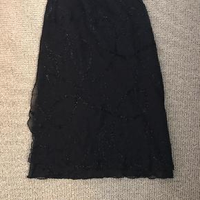 Smuk nederdel fra Elton Stadig i flot stand, evt ny elastik i, da den er lidt løs, men af samme grund kan den passes af en str 38. Ville være flot til nytårsaften grundet glimmermønstret i stoffet.