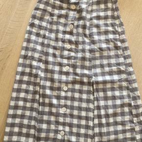 Nederdel med gingham print fra mango med to slidser. Brugt få gange.