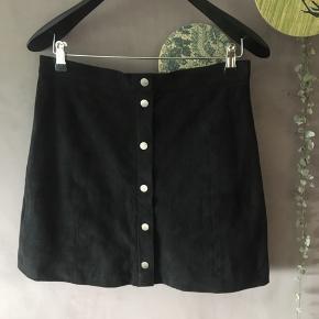 """Nederdel i ruskind """"look-a-like"""" materiale med sølv knapper hele vejen ned. Lukkes med lynlås bagpå. Den er aldrig brugt og sælges kun da jeg ikke kan passe den."""