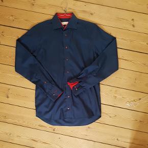 Flot mørkeblå slim skjorte med fede detajler fra mærket John Henric i str 40, købt hos Herrenes Magasin by David K.   Aldrig brugt!   NP 800KR MP 250KR   Kan sendes mod betaling.