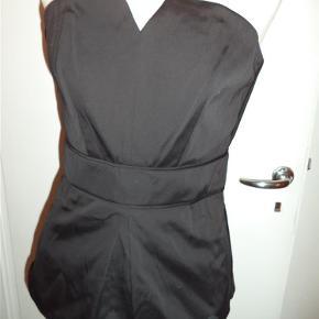 Varetype: Klassisk sort corsage-top, ny! :-) Farve: Sort Oprindelig købspris: 1200 kr.  En smuk og klassisk corsage top. Den lukkes bag på med guld-lynlås. Der er siliconebånd foroven til at holde den oppe. Taljeret og med flot udskæring foran. Også fin med en hvid skjorte under! Talje måler 34,5 cm x 2 og bryst måler 41 cm x 2 plus ekstra (svært at måle, da der er mere stof foran ved brystsyninger). Jeg kan fint lukke den og jeg måler 88 cm... Den er i satin(af den gode kvalitet) og foret.  Ny og med tags. Kan prøves på i Odense C. ______________________________________________  Se også mine andre annoncer og byd gerne på flere ting samlet.