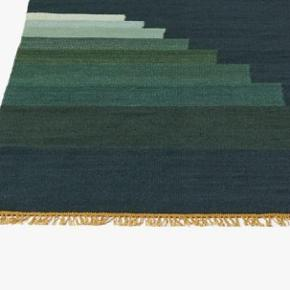 Det fantastiske Another Rug fra &traditions i farven Green Jade - 170*240 cm. Produceret i 80 uld og 20 bomuld.   To år gammelt, men reelt kun anvendt i et, hvorfor det fremstår i meget god stand. Dog et enkelt tryk fra et sofaben - se billede 3. Det første billede (lånt fra nettet viser bedst farven som den fremstår i virkeligheden).   Nypris 4.495 kr.