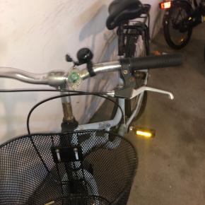 Blå børnecykel med kurv. Dæk er flade