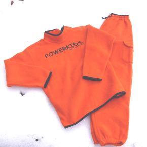 Orange fleece sæt m. marineblå kanter. Bukserne har både elastik og snøre i linningen.  Lommer m. velcrolukket klap på begge bukseben. Skridtlængde ca 53 cm. Trøjen har knaplukning Hals-skulder. Ærmelængde ca 35 cm. (Bemærk også anden annonce på samme sæt i str. 10 år)  Kan også sendes mod betaling af porto, og evt. fragtes til afhentning i København.