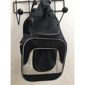 Transporttaske i nylon af høj kvalitet Mål: 30x26x33 Op til 10 kg. Kan åbnes i front og top Meget komfortabel pga. Regulerbar sele ved talje og skulder. Integreret Line forhindre at dyret springer ud. Kan anvendes til hund og kat. Aldrig brugt. Nypris: 450