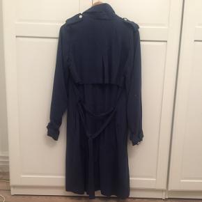 Frakke fra VILA i mørkeblå, str S. Knapper foran og bindebånd i taljen. Aldrig brugt, nypris 600kr. Kan sende med DAO, køber betaler porto Sletter annoncen når varen er solgt