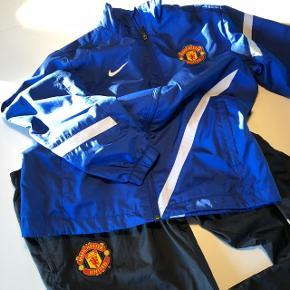 Manchester United. Blå og sort træningsdragt. Str. 152/158. Foret og med snører i bukseben.