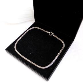 Flot Halskæde i mesh der skinner flot, når der kommer lys på.  Halskædens fulde længde er 47 cm.  Låsens diameter er 1,5 cm, selve kædens tykkelse er 4,5 mm. Stemplet MAGAR og 925. Vægt: 25,5 g (æsken vejer 125 g)  Jeg har også et armbånd der passer til til salg. Samlet køb 400 kr.  Se også mine andre annoncer med smykker :)