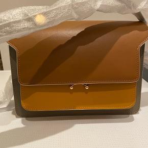 Smuk Marni taske i glat læder, tasken er multi farve af brun, grå og ochre. Jeg sælger udelukkende grundet pengemangel - tasken hsr blår foer indvendigt i bomuld, super fint match. Brugt en enkelt gang.  Repsketer venligst at jeg ikke bytter og køber betaler porto samt gebyr ved tspay.