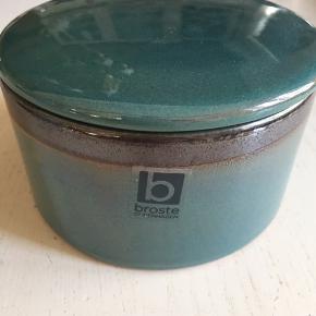 Lille opbevaring med låg fra Broste i en lækker mørkegrøn farve og en brun kant foroven. Er lavet i keramik og måler Ø12 cm og ca 7 cm høj