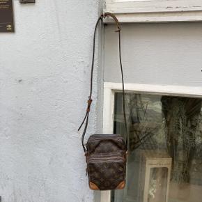 Vintage Louis Vuitton Amazone Crossbody taske af Monogram Kanvas.  Der medfølger ikke originalt købstilbehør til tasken.  Tasken fremstår i flot velholdt stand, med naturlige brugsspor og patina.  Tasken måler ca 15×21 cm.
