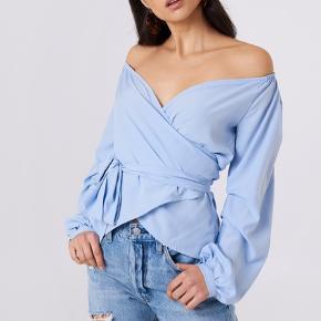 Super fin wrap off-shoulder bluse / top i lyseblå. Har kun været brugt en gang og er derfor i rigtig god stand.